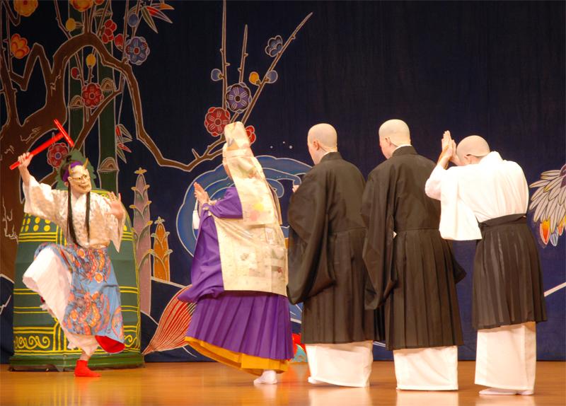 組踊「執心鐘入」の一場面。鬼女に姿を変えた宿の女(左)を法力で鎮めようと、寺の座主と小僧たちは戦いを挑む=北谷ニライセンター
