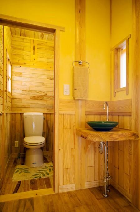 ホールの床はイタジイ、壁と天井はリュウキュウマツ。トイレ床はイタジイ、壁と天井はクスノキで、床柱にはイジュの木を使った沖縄の木霊が響く家(沖縄市諸見里)