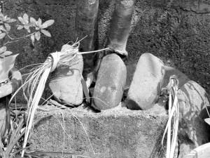 3個の石を横一列に並べた最も古い形の屋敷神。(大宜味村塩屋)写真提供/むぎ社