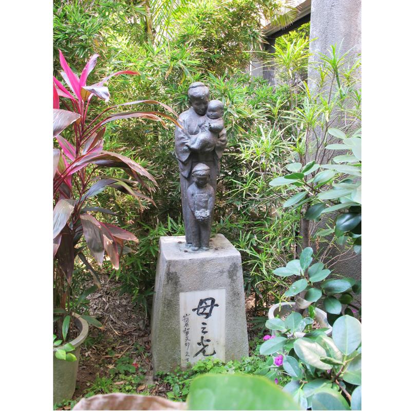 正面玄関左側、前庭に置かれている「母之光」像。この建物が完成した直後に設置された。山梨県知事天野久の名が刻まれている