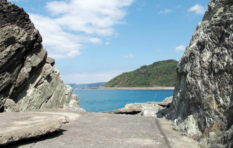 <2> 岩を切り開いて建設された道。コンクリートの舗装が波でめくり上がり崩れている