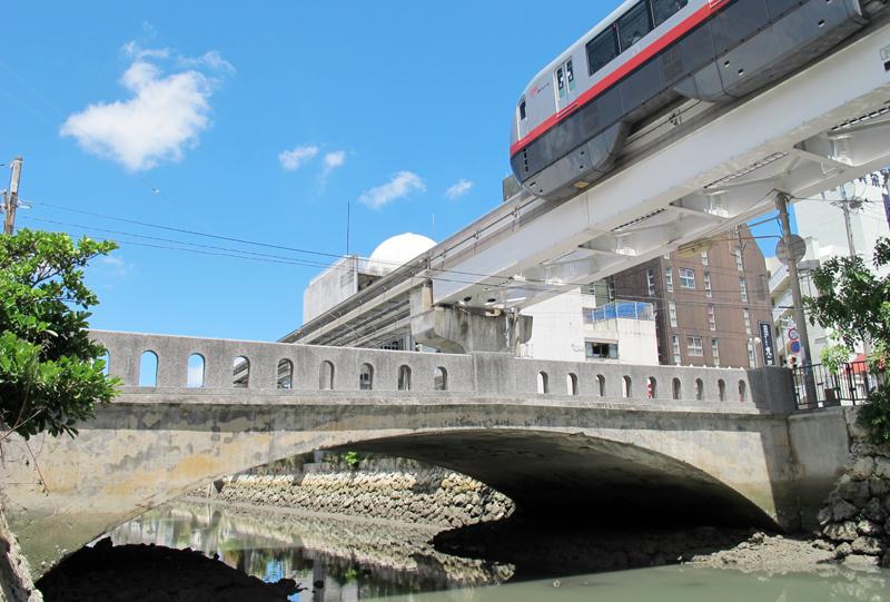 <6>久美橋。向かって左側が久茂地町、右側が美栄橋町。両者を結び、頭文字を取って名付けられた。奥の白いドームが旧久茂地公民館