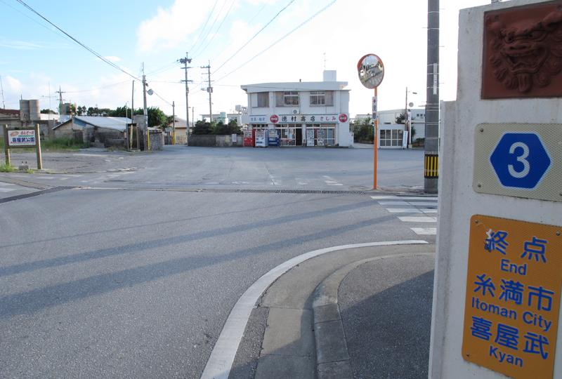 商店、郵便局、バスの折返所に囲まれた広場が、喜屋武集落の中心。立派な農協の建物も残っていた。付近で旧3号線の痕跡を示すものを探したが、何もなかった