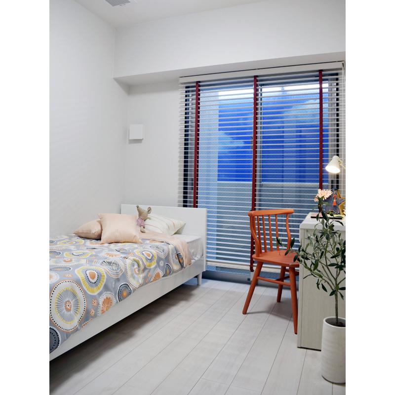 子ども室のベッドカバーは、ブラインドとイスの色みに合わせ明るく元気な雰囲気に