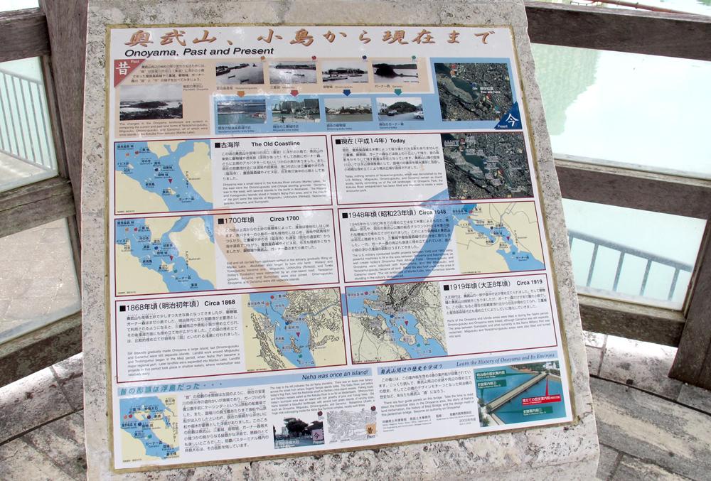 <2>奥武山公園には周辺の史跡や埋め立ての経緯を説明した案内板が設置されている。ガーナー森の昔の写真を見ると、確かに小高い森から砂州が伸びている