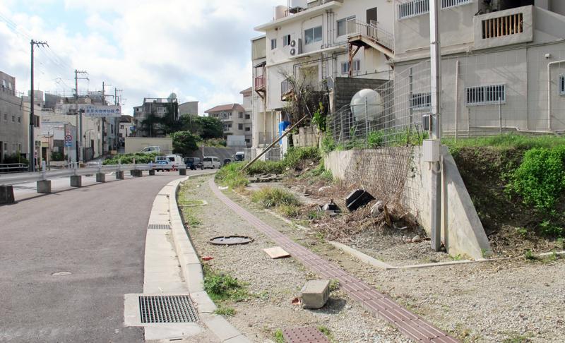 <1> 那覇市牧志、桜坂付近の道路建設現場。丘を切り崩して延びる道路の左右に、道路用地に切り取られて残された、いびつな形の土地が残る