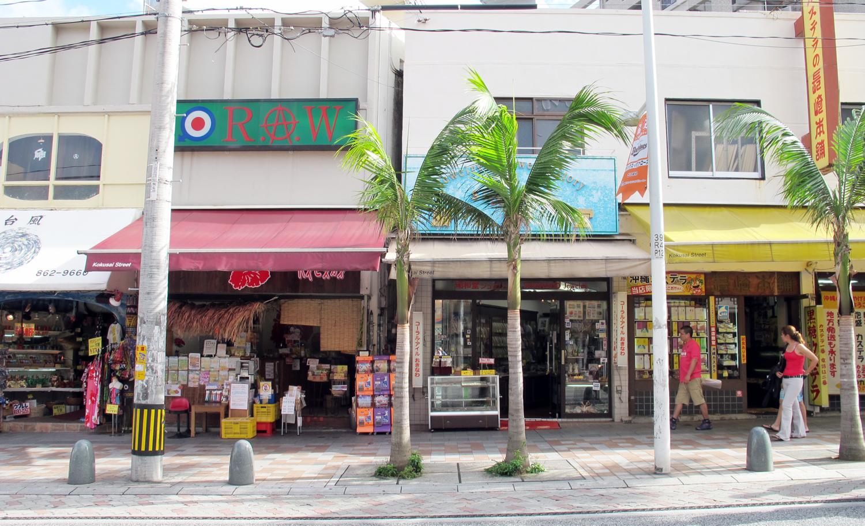 <3> 一見何でもない店が並ぶ風景だが、よく見ると中央の店の棚が道に面して斜めになっているのが見える