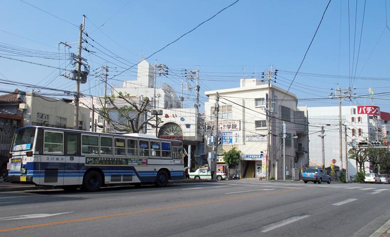 <写真1>開南交差点。バス停や商店街の入り口が集まる、南部からの那覇中心部への玄関口。道路拡張に伴う工事で、周囲の建物が取り壊され、日々風景が変化している