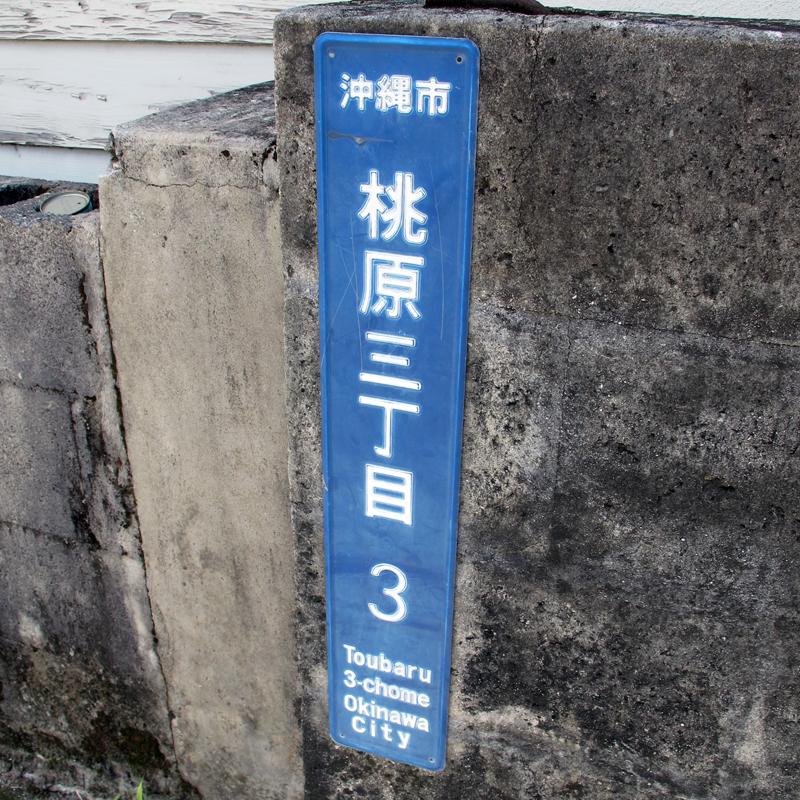 <2>写真1の住所板をズームアップ。見ると住居表示板で「桃原三丁目」と書かれてあり、泡瀬地区にない「泡瀬」バス停であることが分かる