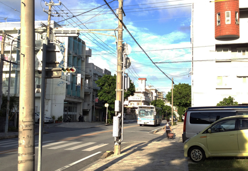 <1> 「プール入口」バス停があった付近。一番手前にある電柱の辺りと、バスが走っている位置の道向かいビルの前に、かつてバス停が存在した