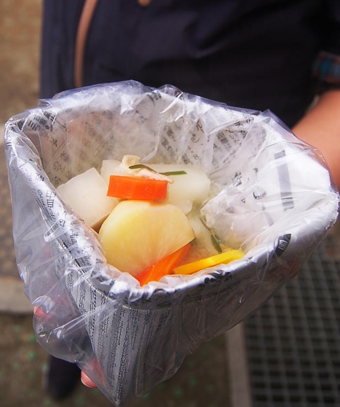 新聞紙で作成した食器をビニールで巻いたもの。豚汁を盛り付けている