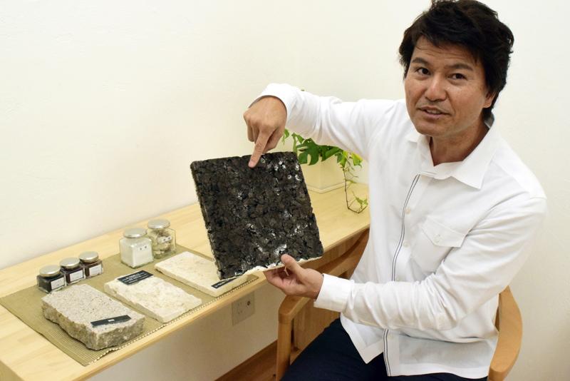 壁の断熱材・炭化コルク材のサンプルを手に説明する金城社長