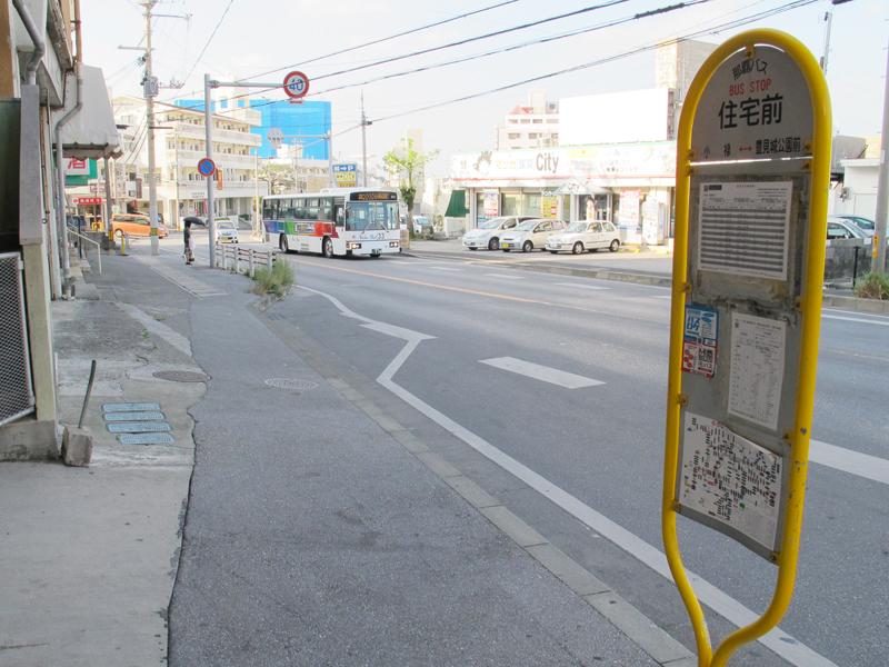 <1>那覇市小禄にある住宅前バス停。住宅地ばかりではなく、周囲にはスーパーなども出店している。バス停の乗り降り、車の通りもほどほどあり、人の行き来も多い