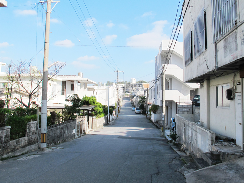 <2>住宅前バス停の近辺の、直線の道路に家屋が並ぶ典型的な分譲地の光景(琉生団地)