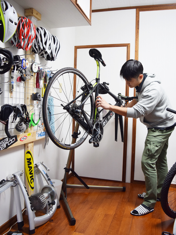 自転車部屋で愛車を整備する宮城さん。壁面収納は、突っ張り式のポールとメッシュパネルを組み合わせて手作りした。ヘルメットなどよく使うものを掛ける