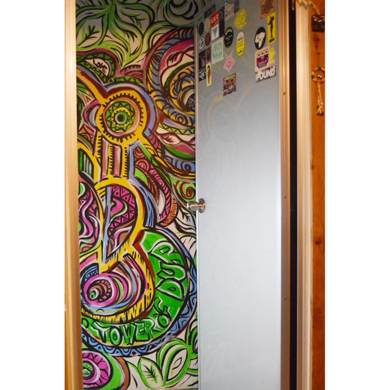 4階玄関の壁面。友人のアーティストによる色彩豊かなアートが印象的。下の「TOWER OF DUB」はスタジオ名