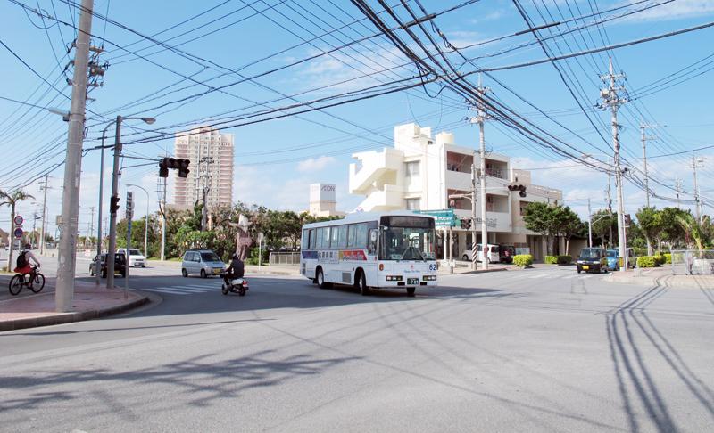 <1> 北谷運動公園前バス停美浜付近の交差点。ここでバスの路線が二手に分かれる。バスの背後にマンションやショッピングセンターが見える。このバスをはじめ、日中以降のバスは、商業施設が並ぶアメリカンビレッジを経由する。奥に向かって直進する道が「北谷運動公園前」バス停を経由する道路