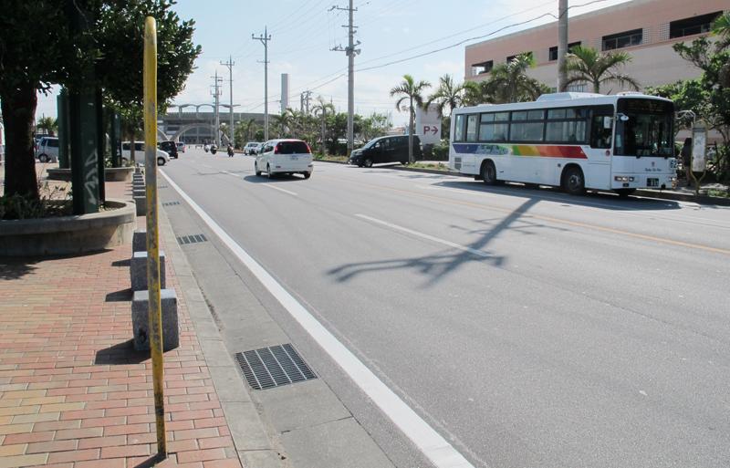 <3> 「アメリカンビレッジ南口」バス停。停車しているバスの右手がショッピングセンター。奥に見えるアーチが北谷公園の入り口。こちらの方が北谷公園に近い
