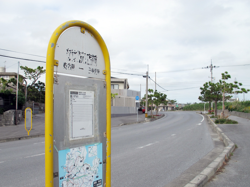 <1> 新城売店前バス停の全景。現在も残る売店はカーブの先に位置している。近くに玉泉洞が位置していることもあり、車の通行量は多い