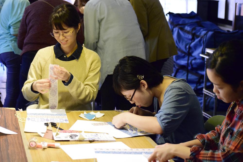美しい模様の入ったマスキングテープを使い、ガーランド作りに挑戦する参加者=2016年2月13日、沖縄市