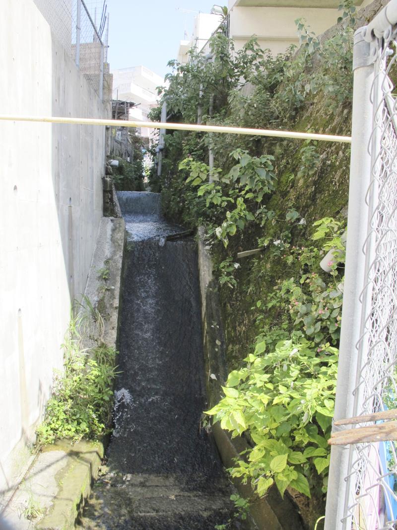 <3> 大道練兵橋以来、姿を現した川。家と家の間を、まるで渓谷のように下る。水も透明で、見た限りではきれいそう。川の流れを見て、繁多川が水の豊かな土地であることを思い出す。