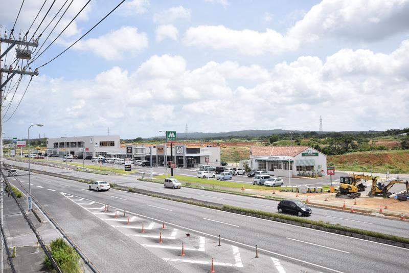 国道58号の西側から開発中の東地区を見る。沿道にはことし4月、飲食店やコンビニ、歯科医院など11店舗が入居するシナジースクエアがオープンし、にぎわう。その奥では道路整備や造成が進められていて、作業中の大型パワーショベルやトラックも多くみられる。