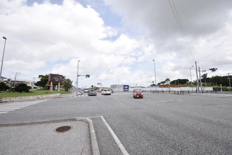 国道58号と県道16号が接する大湾交差点を南側から望む。58号の西側(写真左手)に大湾の住宅地が広がり、東側では区画整理が進む