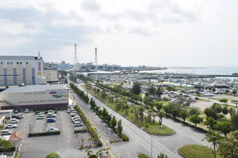 <1>国道58号宜野湾バイパス沿いの高台から、宇地泊地域を望む。海が見える景色の良さが同地域の魅力の一つ。大型商業施設も多く、買い物にも便利。道路も広く、運転しやすい