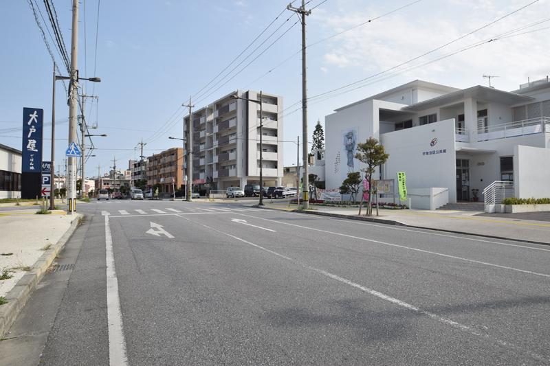 <2>宇地泊公民館前の道は、宜野湾バイパスと国道58号をつないでいる。道沿いには郵便局も移転してきており、交通アクセスと共に、利便性もアップした