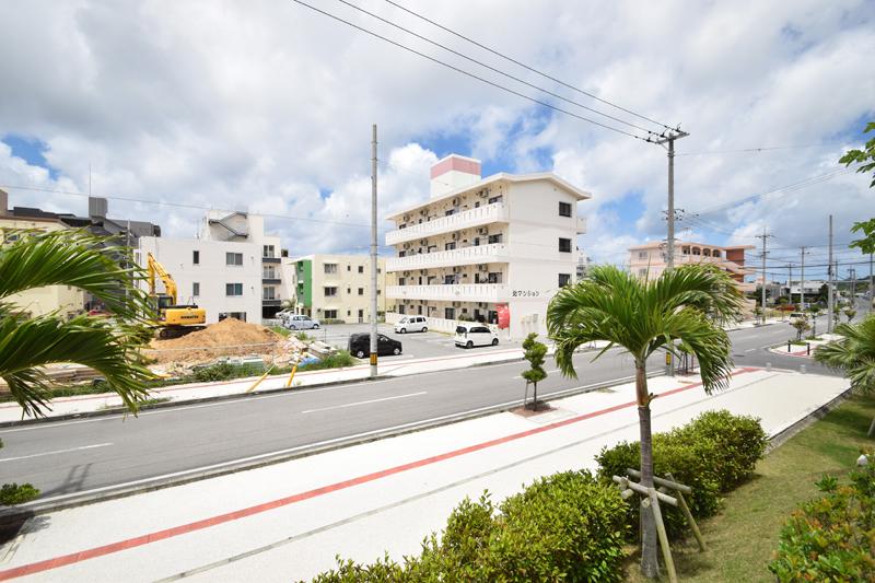 <3>桑江区の北谷町役場周辺。新しいアパートや空き地、工事中の場所も多い。歩道が広く取られ、街路樹も整備されている。車通りは、まだ多くない。