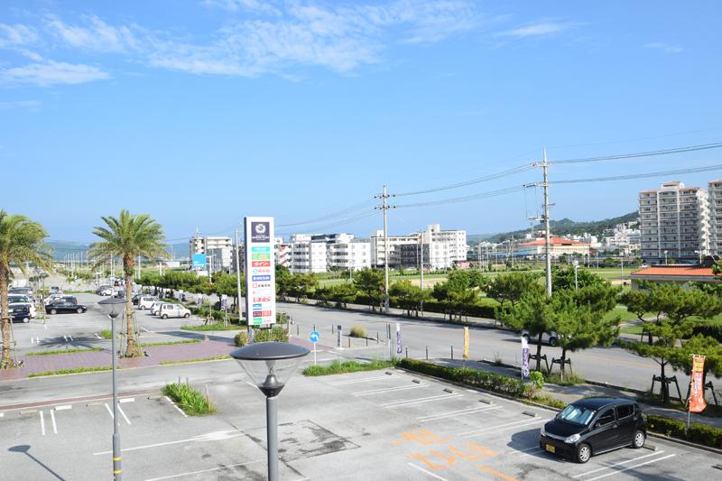 <1>スーパーやホームセンター、飲食店などが入った複合施設「マリンプラザあがり浜」から与那古浜公園を見る。広い公園の向こう側には築浅のアパートが建ち並ぶ。歩道が広く、街路樹もしっかり整備されているので歩きやすい。