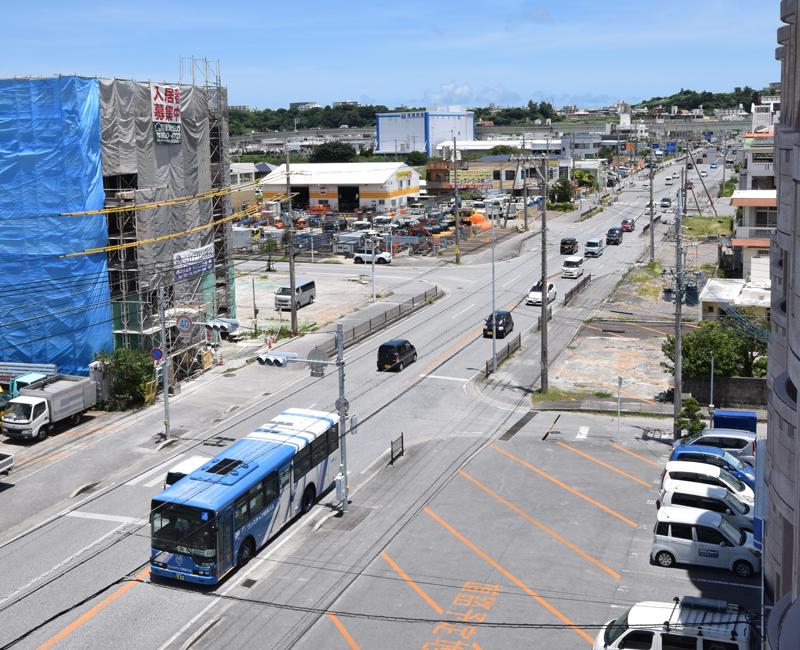 日中でも交通量の多い、伊良波を通る県道256号。沿道ではアパートの新築工事が進んでいるほか、拡幅工事に向けて「道路予定地」と書かれたスペースが続く。右奥に見えるのは、那覇空港自動車道